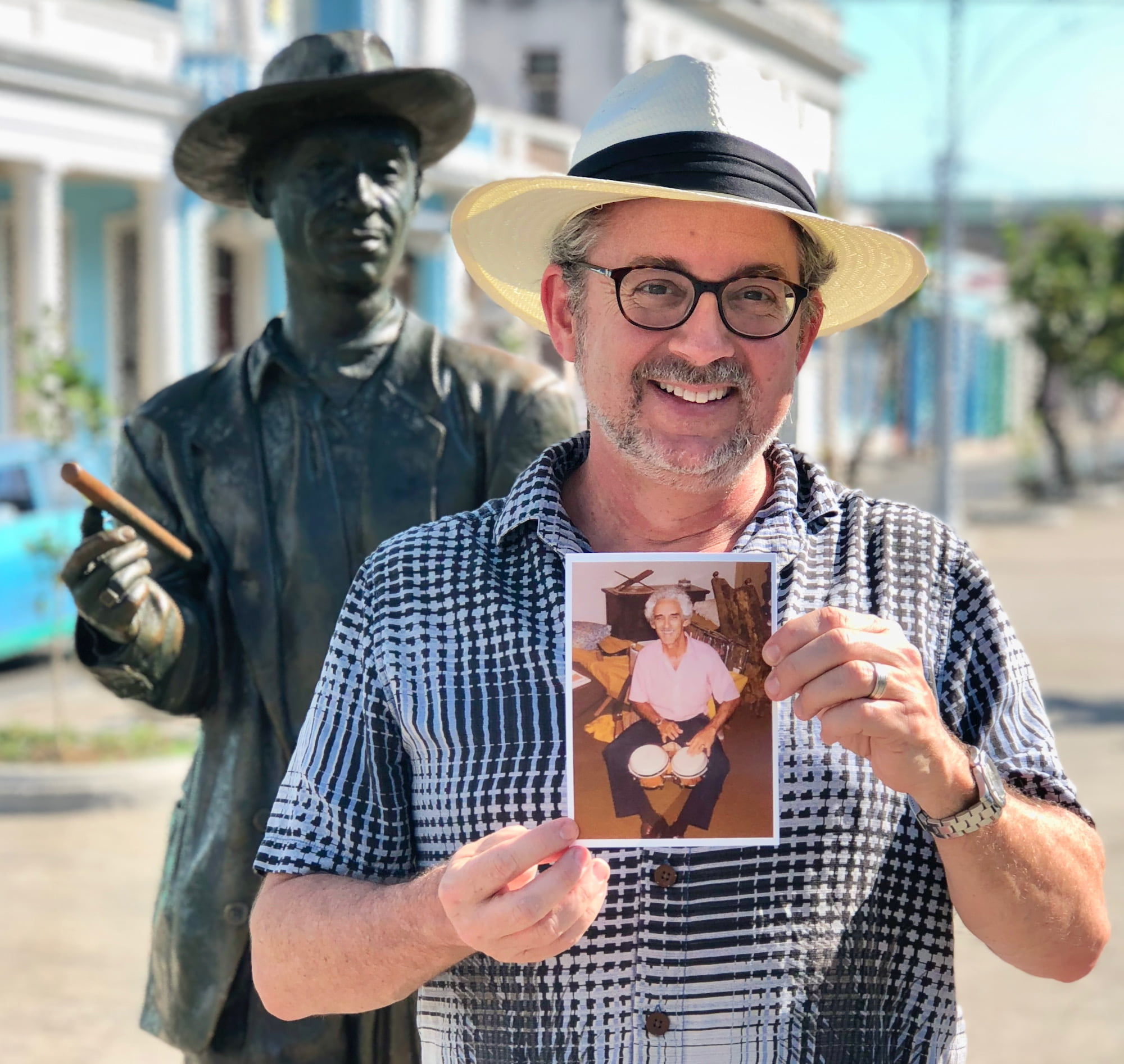 Cuba - Miguel holding a photo of his father at the statue of singer Beny Moré - Cienfuegos